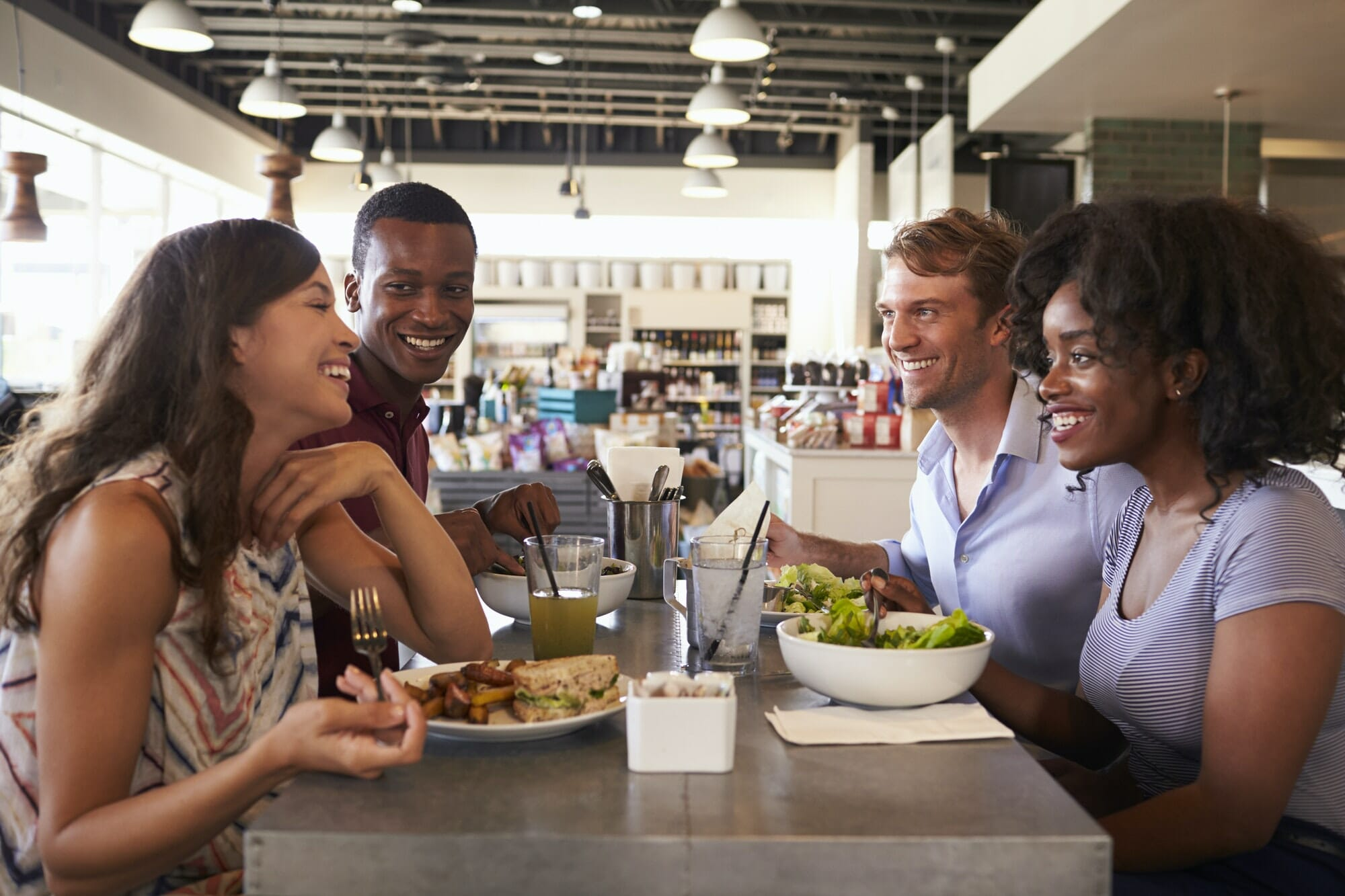 Friends Enjoying Lunch Date In Delicatessen Restaurant